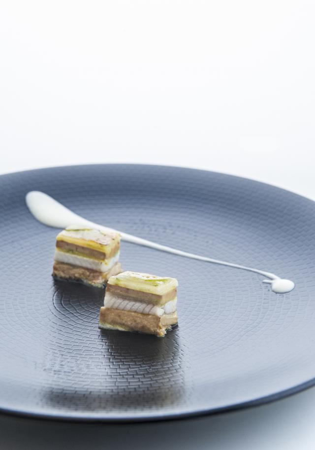Milhojas caramelizado de anguila ahumada, foie gras, cebolleta y manzana verde.